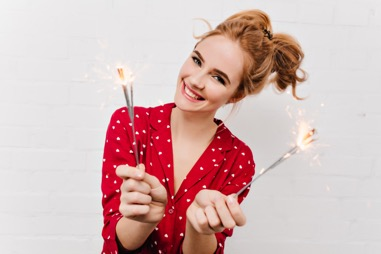 Woman holding sparklers talking about botox, dermal fillers and more