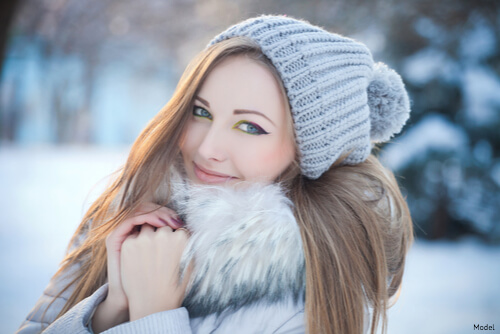 Woman smiling in the snow bundled up