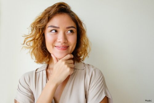 Woman with hand on chin smiling