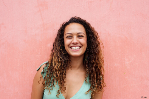 Woman smiling with a pink background